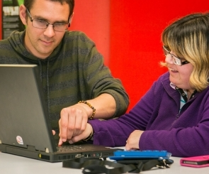 Photo of someone helping a blind person using a computer